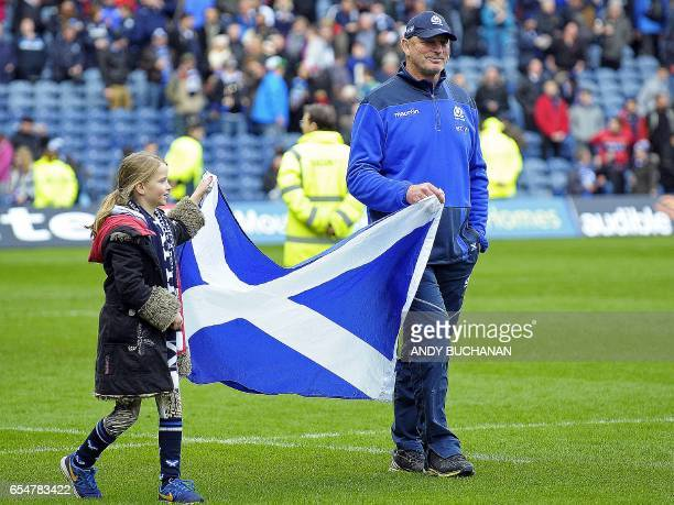 Departing coach Scotland's New Zealand head coach Vern Cotter and his daughter Arabella carry a Saltire the flag of Scotland onto the field after the...