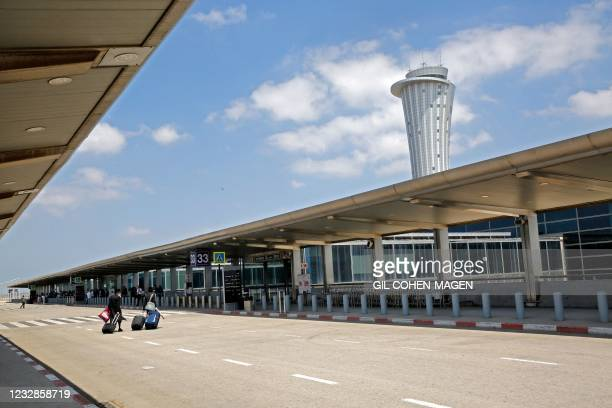 Departing passengers roll their suitcases at the nearly deserted Ben Gurion airport in Lod, near the Israeli coastal city of Tel Aviv, on May 13,...