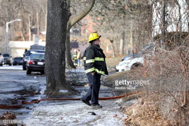 A department member pauses in front of the scene of a 5alarm fire at 7 lowell St in Worcester MA on Dec 9 2018 One firefighter was killed and four...