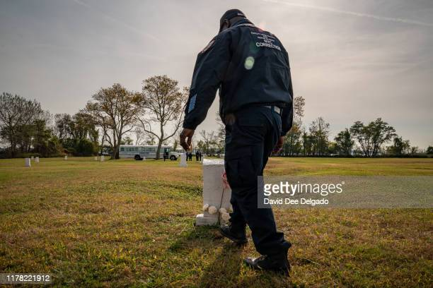 Department of Correction officer walks by flowers laid at a burial marker on Hart Island a former prison and Nike missile silo site which is now the...