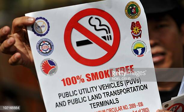 A Department of Health personnel shows an antismoking sticker during the DOH's no smoking campaign that aims to implemant a 100 percent smokefree...