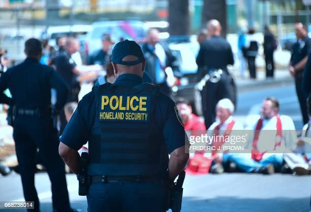 A Department of Homeland Security officer watches as police arrest demonstrators protesting recent enforcement actions by federal Immigration and...