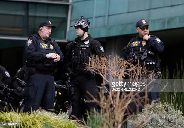 Department of Homeland Security officers watch as protesters gather outside US District Court in Seattle Washington on February 17 before a hearing...