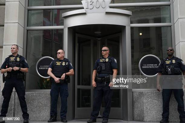Department of Homeland Security police officers stand guard the entrance of the headquarters of US Customs and Border Protection during a protest...