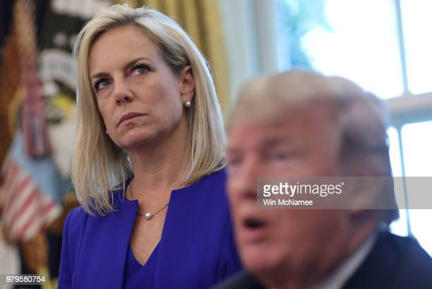 Department of Homeland Security Secretary Kirstjen Nielsen listens as US President Donald Trump answers questions after signing an executive order...