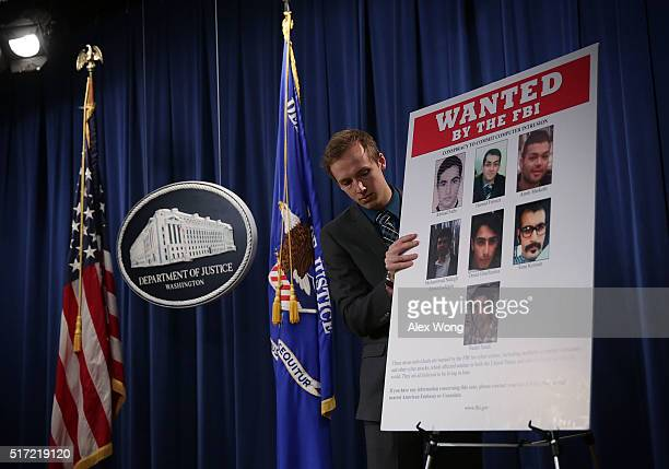 Department of Justice employee put up a poster of the seven indicted hackers prior to a news conference for announcing a law enforcement action March...