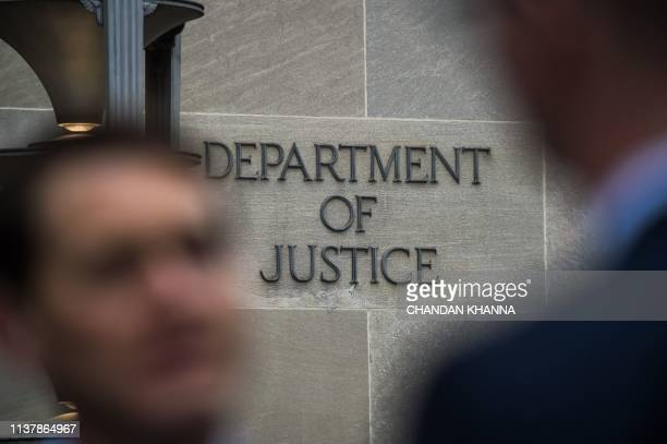 A Department of Justice sign is seen on the wall of the US Department of Justice building in Washington DC on April 18 2019 The final report from...