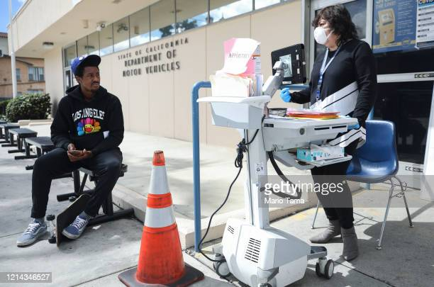 Department of Motor Vehicles worker speaks with a man who did not have an appointment at an appointment desk in front of the DMV building with a cone...