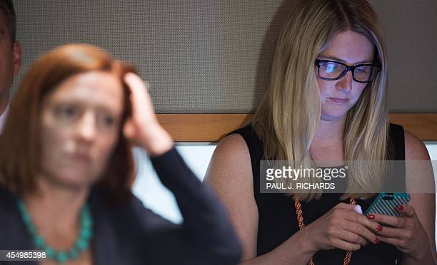 US Department of State spokesperson Jen Psaki listens as US Department of State Deputy Spokesperson Marie Harf works on her phone while US Secretary...