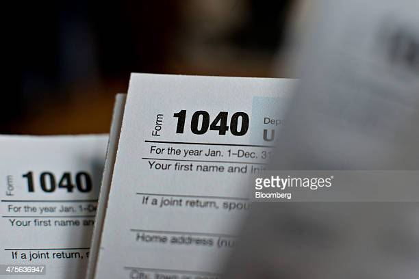 US Department of the Treasury Internal Revenue Service 1040 Individual Income Tax forms for the 2013 tax year are arranged for a photograph in...