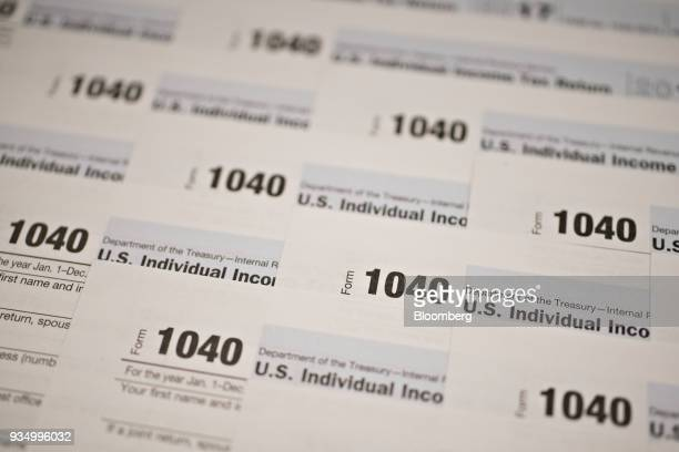 US Department of the Treasury Internal Revenue Service 1040 Individual Income Tax forms for the 2017 tax year are arranged for a photograph in...
