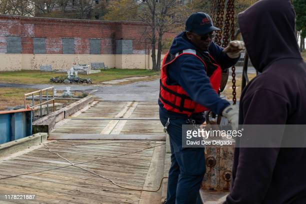Department of Transportation workers maintain the ferry which the is the only accessible route to Hart Island on October 25 2019 in New York City...