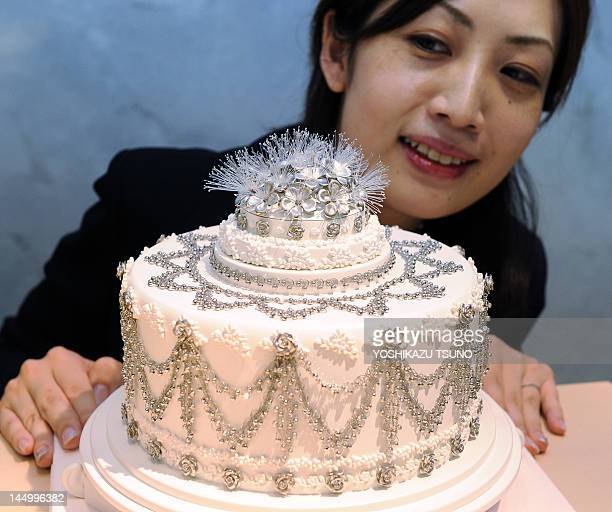A department store clerk displays a 'Platinum Wedding Cake' decorated with a total of 400g of platinum jewelry produced by Platinum Guild...