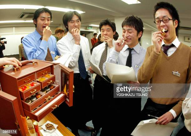 Department store male employees try to taste samples of chocolates from a large jewel box shaped chocolate package priced 20000 yen in Tokyo 13...