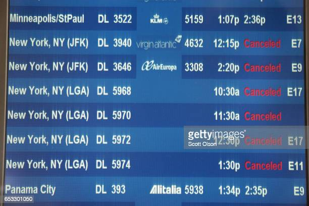 A departure board at O'Hare International Airport shows all flights to New York City canceled on March 14 2017 in Chicago Illinois A snowstorm is...