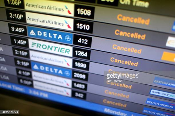 A departure board lists cancelled flights at Miami International Airport on January 26 2015 in Miami Florida Northeast coast airports are canceling...
