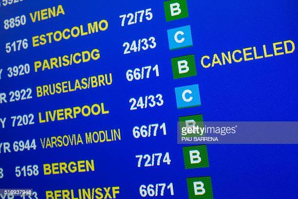 A departures board informs travellers of the cancellation of a flight to Brussels at Barcelona El Prat airport following attacks in Belgian capital...