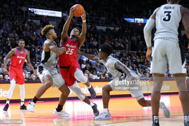 DePaul Blue Demons forward Femi Olujobi defended by Providence Friars center Nate Watson and Providence Friars guard Maliek White during a college...
