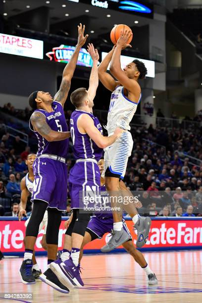 DePaul Blue Demons guard Eli Cain shoots over Northwestern Wildcats guard Bryant McIntosh and Northwestern Wildcats center Dererk Pardon during the...