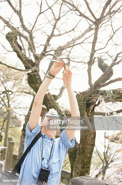 Depeche Mode David Gahan tying paper fortune on a tree at Kiyomizu temple in Higashiyama Kyoto, Kyoto, April 1985.