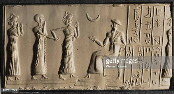 Depiction of a bare deaded worshipper being led by a minor goddess into the presence of a seated man possibly the deified U Nammu King of Ur The...