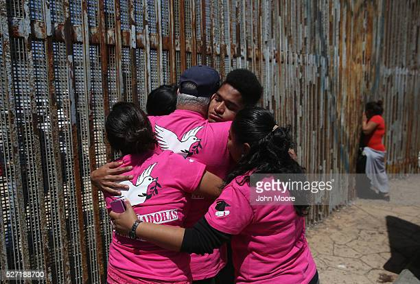 Deported family members of Dreamers and their supporters pray at the USMexico border fence on May 1 2016 in Tijuana Mexico Dreamers are USborn...