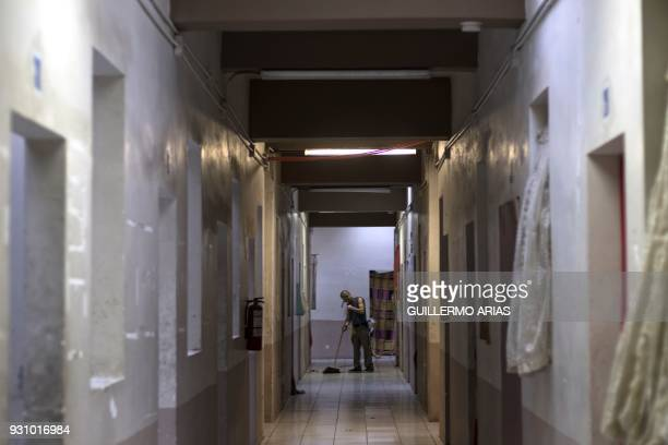 TOPSHOT A deported man sweeps a corridor at the Hotel del Migrante in Mexicali Baja California state Mexico on March 10 2018 President Trump is...