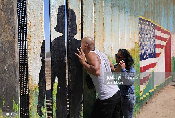 A deportee in Mexico speaks through the USMexico border fence to loved ones on the American side on September 25 2016 in Tijuana Mexico US Border...