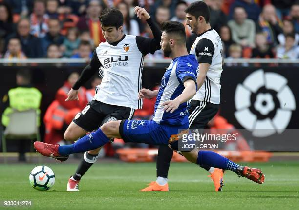 Deportivo Alaves' defender Ruben Duarte vies with Valencia's midfielder Carlos Soler during the Spanish League football match between Valencia CF and...