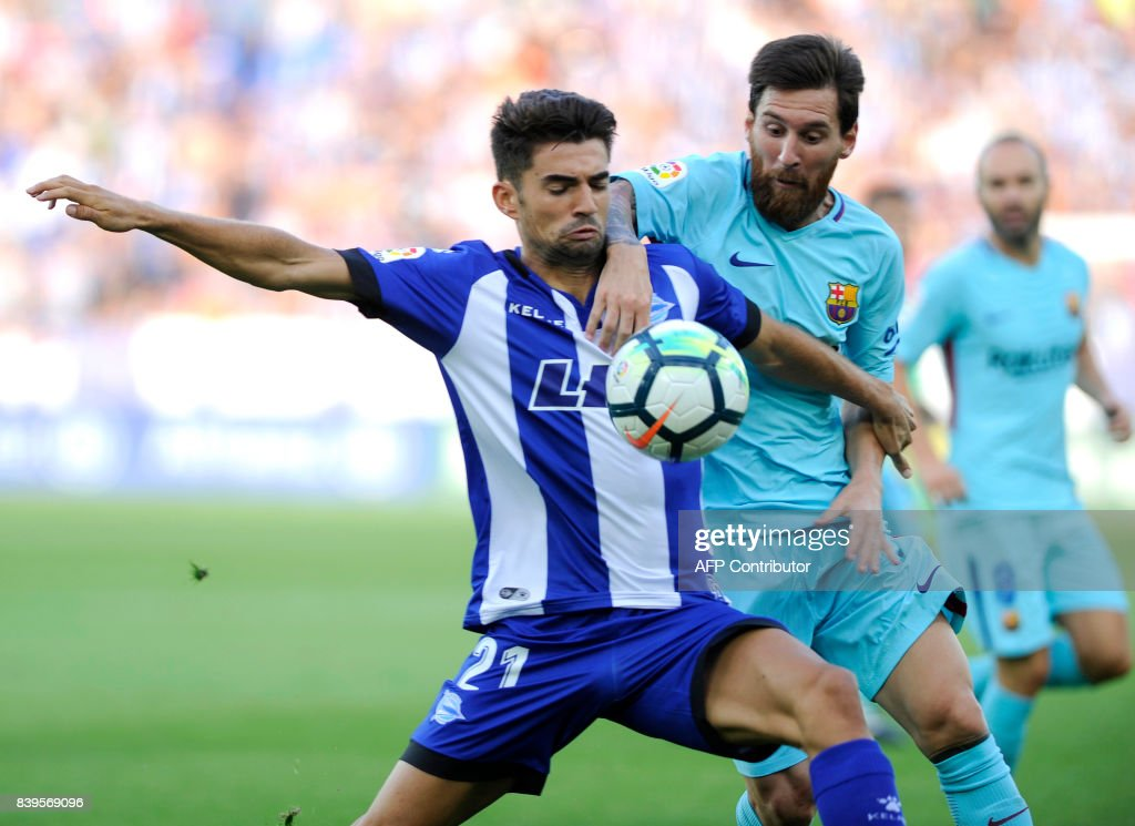 Deportivo Alaves' midfielder Enzo Fernandez (L) vies with Barcelona's Argentinian forward Lionel Messi during the Spanish league football match Deportivo Alaves vs FC Barcelona at the Mendizorroza stadium in Vitoria on Agust 26, 2017. / AFP PHOTO / Ander GILLENEA