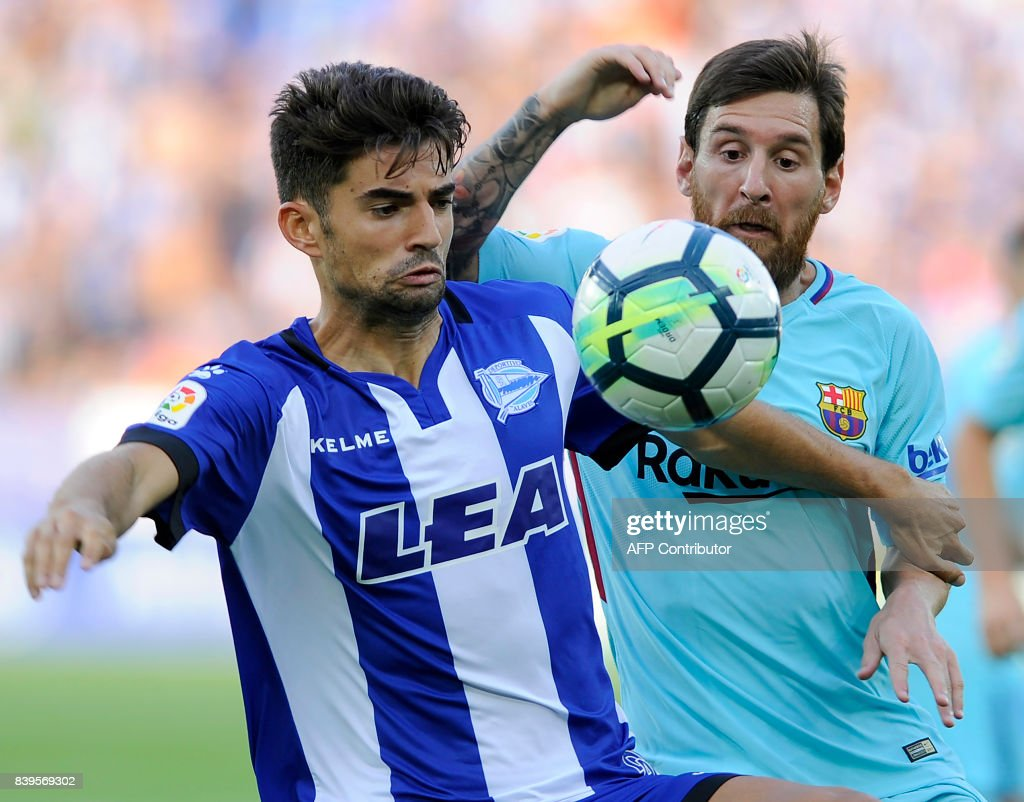 Deportivo Alaves' midfielder Enzo Fernandez (L) vies with Barcelona's Argentinian forward Lionel Messi during the Spanish league football match Deportivo Alaves vs FC Barcelona at the Mendizorroza stadium in Vitoria on August 26, 2017. /