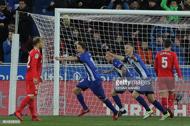 Deportivo Alaves' midfielder Manu Garcia celebrates with teammates after scoring a goal during the Spanish league football match between Alaves and...