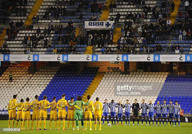 Deportivo Coruna's players and Malaga's players observe a minute's silence for a football fan who died following clashes near Atletico Madrid's...