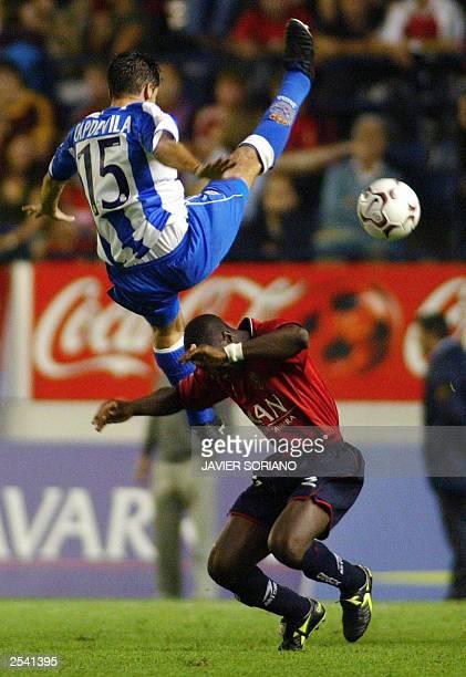 Deportivo de la Coruna's Joan Capdevila jumps on Osasuna's Ibrahim Bakayoko of Ivory Coast during their spanish League match held in El Sadar stadium...