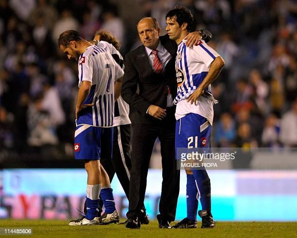 Deportivo de la Coruna's midfielder Juan Carlos Valeron is embraced by Deportivo de la Coruna's coach Miguel Angel Lotina at the end of the Spanish...