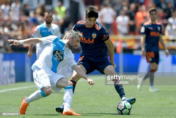 Deportivo La Coruna's Portuguese defender Luisinho vies with Valencia's Spanish midfielder Carlos Soler during the Spanish league football match...