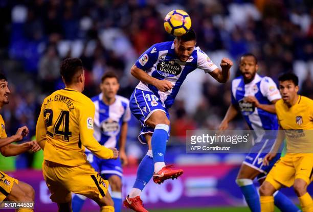 Deportivo La Coruna's Romanian forward Florin Andone heads the ball next to Atletico Madrid's Uruguayan defender Jose Maria Gimenez during the...