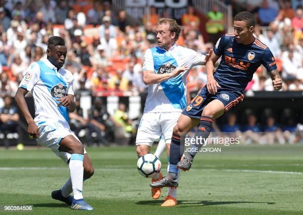 Deportivo La Coruna's Spanish defender Mujaid Sadick Aliu and Deportivo La Coruna's Danish midfielder Michael KrohnDehli vie with Valencia's...