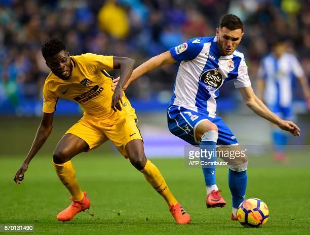 Deportivo La Coruna's spanish forward Lucas Perez vies with Atletico Madrid's Ghanaian midfielder Thomas Partey during the Spanish league footbal...
