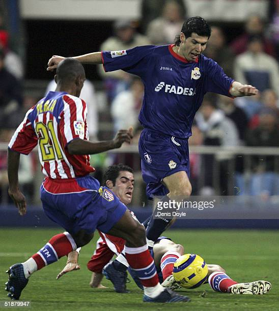 Deportivos Alberto Luque tries to dribble the ball past Atleticos Luis Perea and Antonio Lopez during an Atletico Madrid v Deportivo La Coruna...