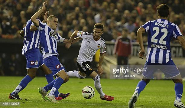 Deportivo's midfielder Alex vies with Valencia's Argentinian forward Pablo Piatti during the Spanish league football match Valencia CF vs RC...