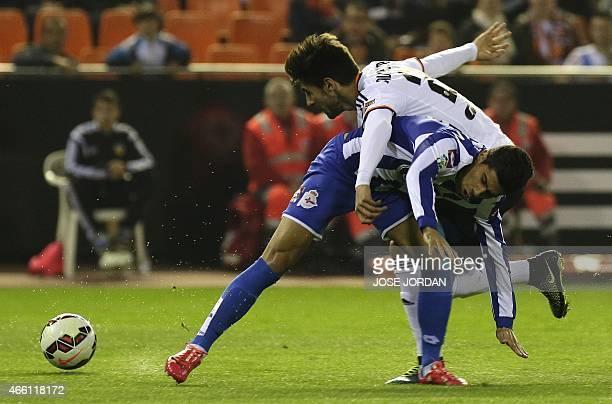 Deportivo's midfielder Juanfran Moreno vies with Valencia's Portuguese midfielder Andre Gomes during the Spanish league football match Valencia CF vs...