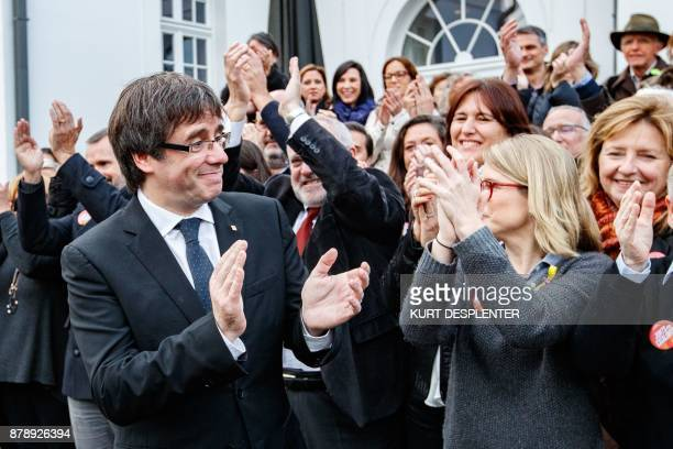 Deposed Catalan leader Carles Puigdemont applauds as he unites to pose with his fellow candidates after a press conference in Oostkamp near Brugge on...