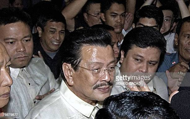 Deposed Philippine president Joseph Estrada flanked by his two sons Senator Jose Ejercito Estrada and Mayor Jose Victor Estrada leaves the...