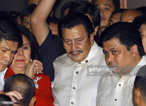 Deposed Philippine president Joseph Estrada flanked by his wife former senator Luisa Ejercito and son Senator Jose Ejercito Estrada is escorted by...