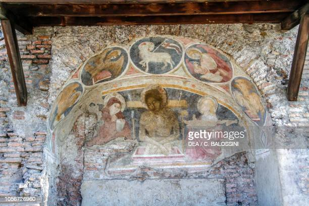 Deposition of Christ between Virgin Mary St John with the Evangelists symbols and Agnus Dei on the arch 14th century frescoes in the church of San...