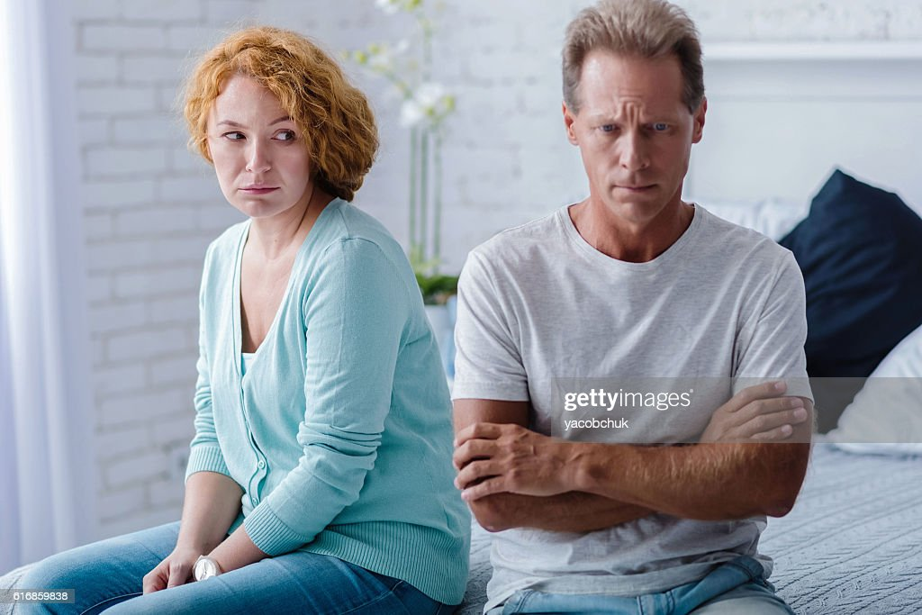 Depressed aged husband and wife sitting on the bed : Stock Photo