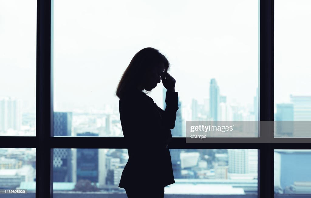 Depressed asian business woman standing at windows with city view background : Stock Photo