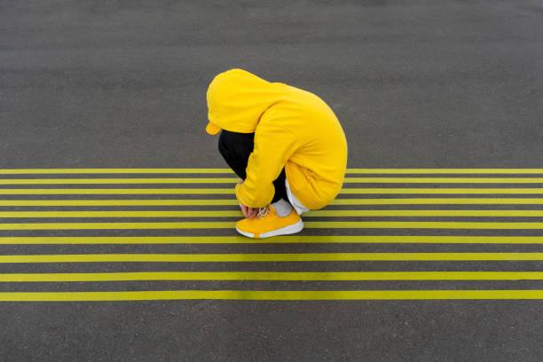Depressed boy crouching on striped yellow road markings