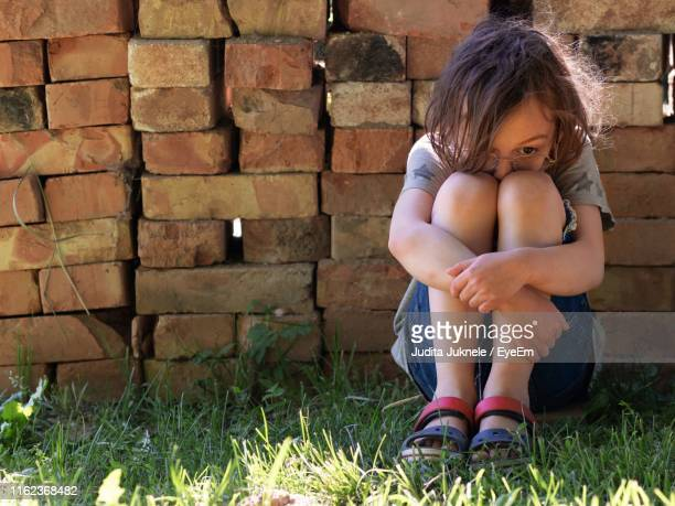 depressed boy hugging knees while sitting on grass against brick wall - hugging knees stock pictures, royalty-free photos & images